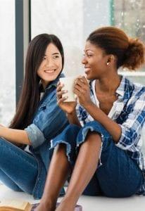 Egy afroamerikai és egy ázsiai hölgy ül és egymásra mosolyog. A jobb oldali, göndör hajú hölgy egy csészét tart a kezében.