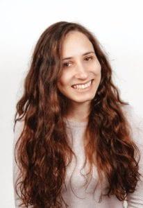 A képen egy mosolygó magyar lány található, aki a göndör, ápolt és vastag hajával tűnik ki a hétköznapokból